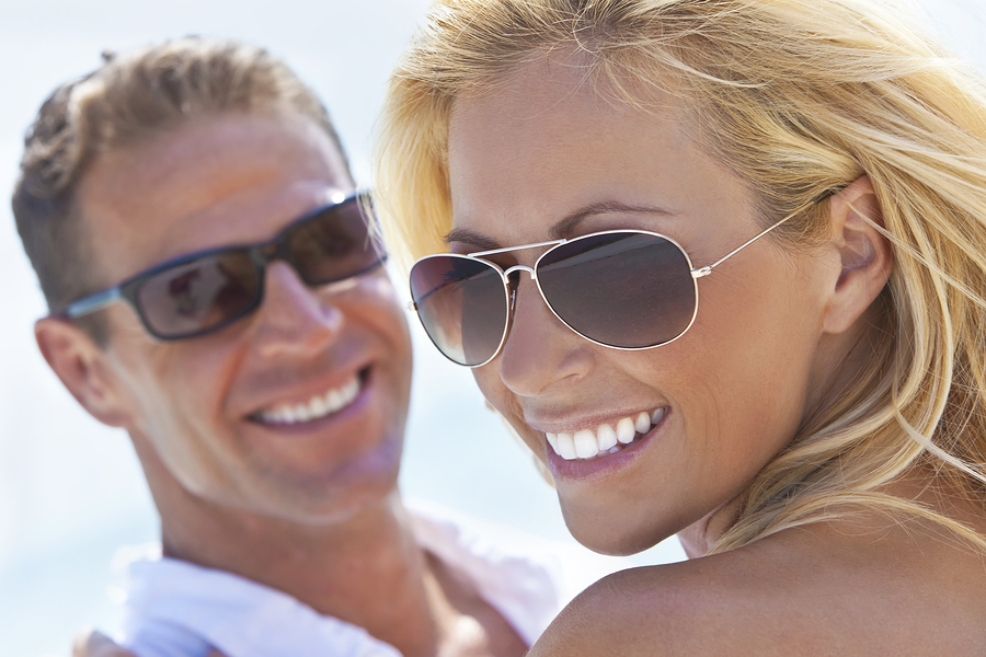 Happy Attractive Woman and Man Couple In Sunglasses At Beach